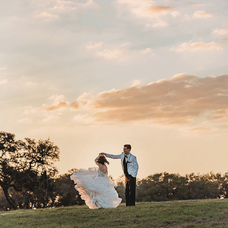 Husband spins wife outside on the grass in the sunset