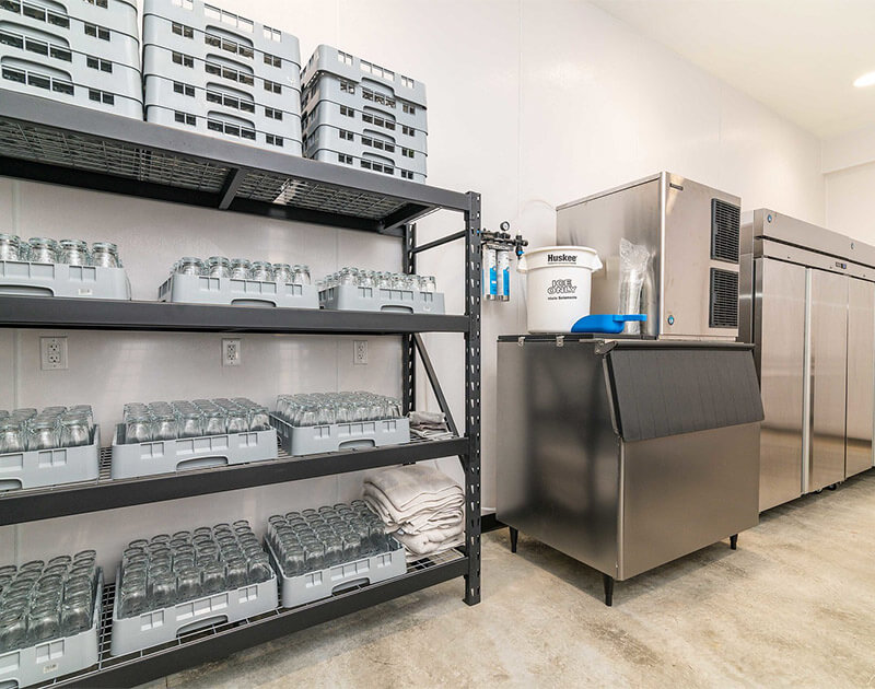 Inside of kitchen showing the glasses racks and ice maker