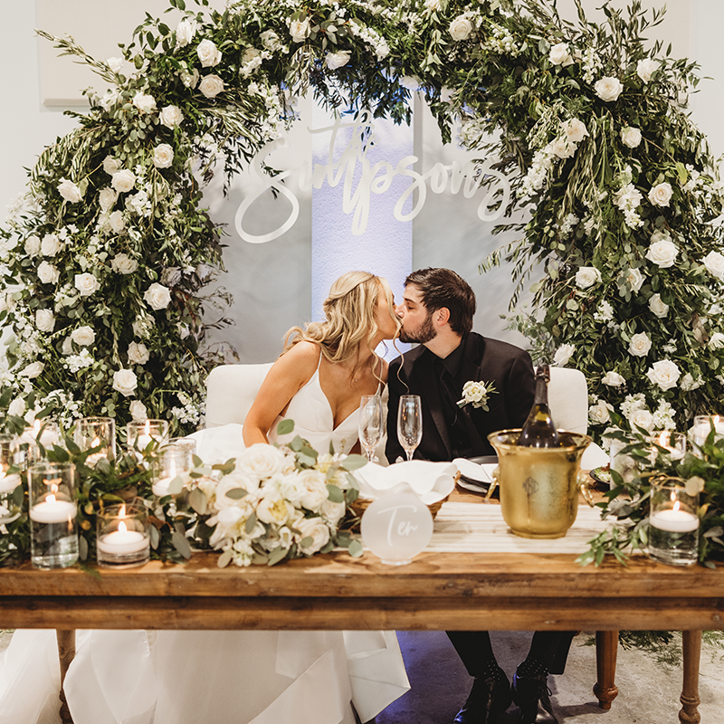 Photo of a Bride and Groom Kissing at Head Table
